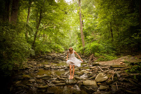 Mid adult woman standing barefoot on rocky riverbed twirling hem of white dress, looking down