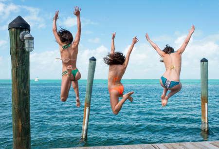 Rear view of three young woman jumping from sea pier, Islamorada, Florida, USA