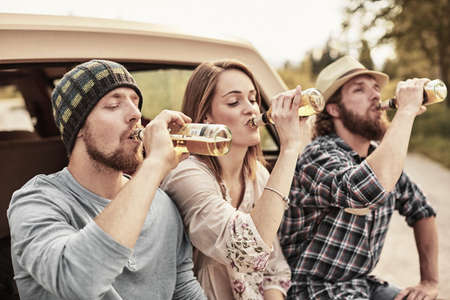 liberating: Three people drinking bottled beer in unison LANG_EVOIMAGES