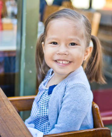 seating area: Portrait of girl with pigtails in sidewalk cafe highchair LANG_EVOIMAGES