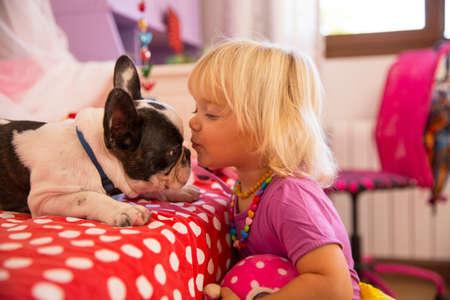 Female toddler kissing cute dog in bedroom