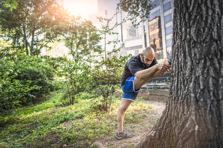 Mature man wear sport clothes stretching leg against tree