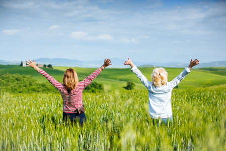 54: Rear view of mature female friends with arms raised in wheatfield, Tuscany, Italy