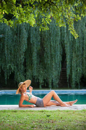 obscuring: Woman lying by pool LANG_EVOIMAGES
