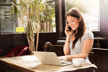 Mid adult woman sitting using laptop and smartphone smiling