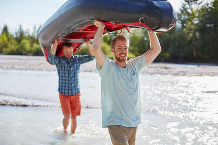 all under 18: Two men carrying dinghy above their heads through shallow water