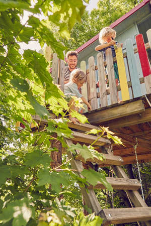 Father and two sons, painting tree house, low angle view