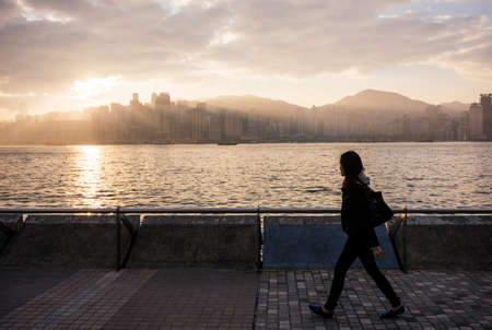 Side view of young woman walking past water, Hong Kong, China LANG_EVOIMAGES