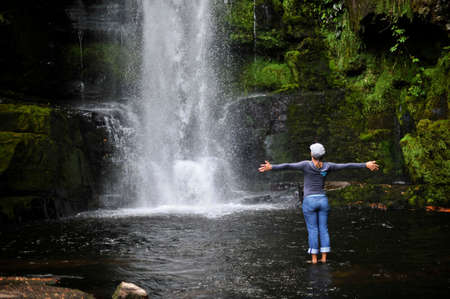 Woman standing by waterfall with arms out, New Zealand
