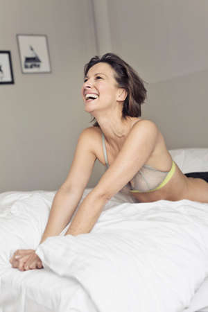 Mature woman wearing bra laughing in bedroom