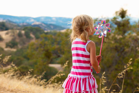 Girl blowing pinwheel, Mt Diablo State Park, California, USA