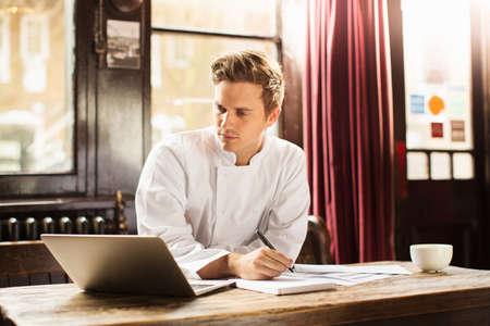 Young man wearing chef uniform using laptop