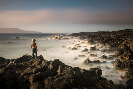 Boy on edge of cliff, Madalena, Pico, Azores, Portugal LANG_EVOIMAGES
