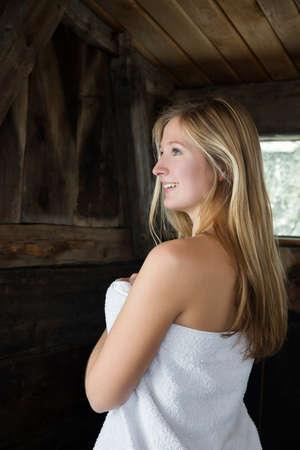 Junge Frau, die in der Sauna eingewickelt im weißen Tuch steht LANG_EVOIMAGES