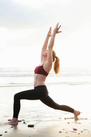 Mid adult woman practicing warrior pose with arms raised on beach