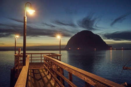 getting out: Silhouetted view of Morro Bay Rock and pier at dusk, Morro Bay, California, USA