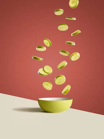 Fresh sliced lemons dropping into yellow bowl LANG_EVOIMAGES