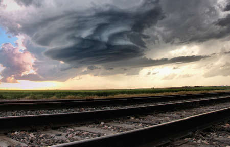 perilous: Fascinating mesocyclone rotating, crystal blue skies and bright sunshine in background, train tracks in foreground, Sidney, Nebraska, USA
