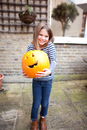 Smiling girl holding heavy halloween pumpkin in garden