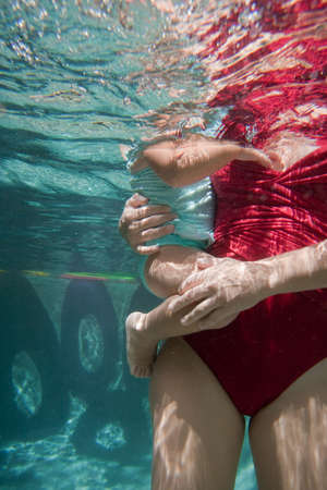 3 4 years: Mother holding daughter underwater in swimming pool