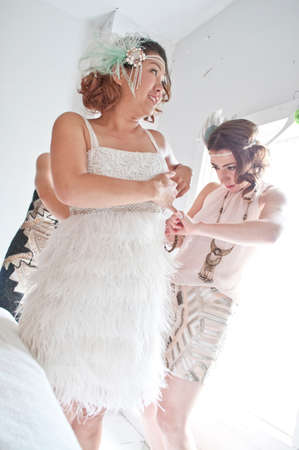 marrying: Two friends helping bride get ready for wedding, low angle view