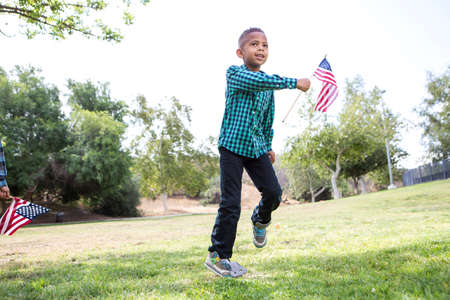 Děti hrající s americkou vlajkou v parku LANG_EVOIMAGES