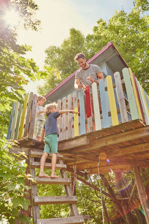 exerting: Father and two sons, painting tree house