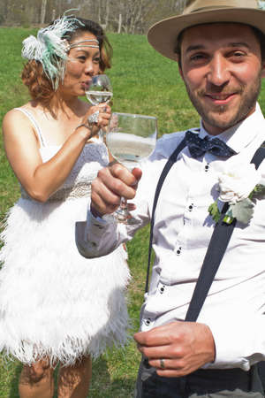 Bride and groom standing in field, drinking wine, smiling LANG_EVOIMAGES