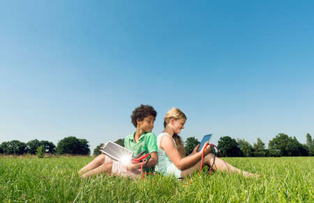 Girl and boy sitting back to back in field using digital tablets
