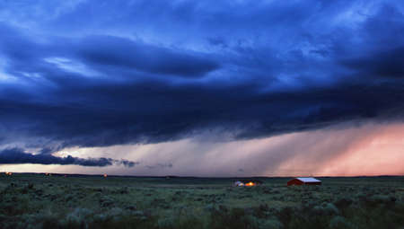 environmental issues: Fluorescent blue sky, final reds of sunset in rain shafts, Wray, Colorado, USA