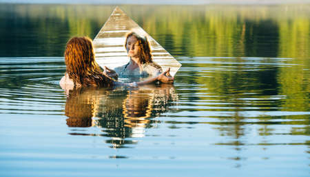 mirror image: Young woman standing in lake, holding mirror, looking at reflection