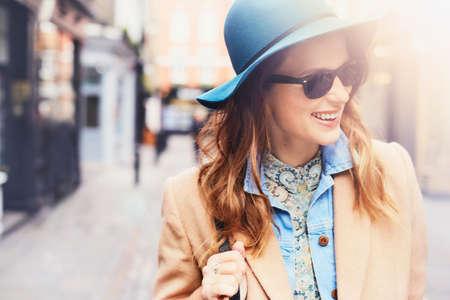 Tragender Filzhut und -Sonnenbrille des modernen jungen weiblichen Käufers, London, Großbritannien