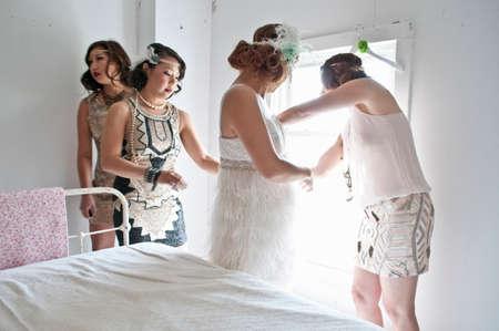 Friends helping bride get ready for wedding