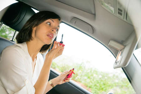 Businesswoman putting on mascara in car