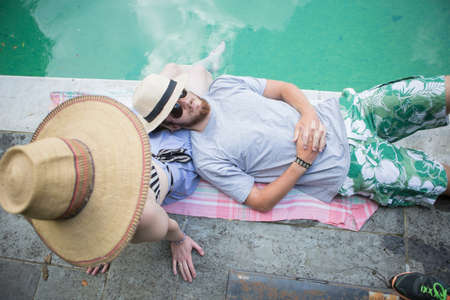 obscuring: Couple relaxing on blanket beside pool