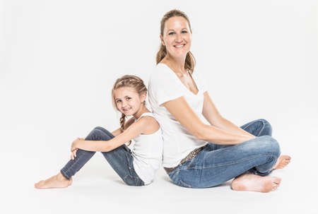 Portrait of mother and daughter sitting back to back