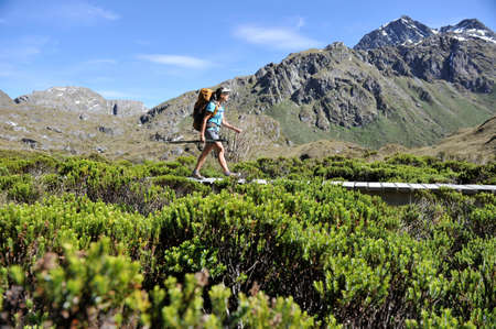 getting out: Woman hiking on boardwalk, New Zealand