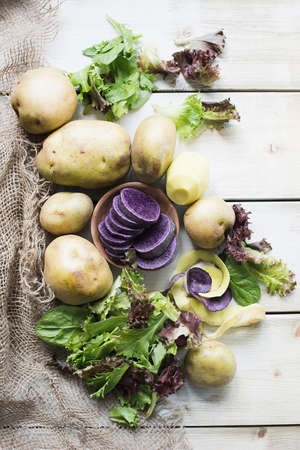 Peeled potatoes with salad, overhead view