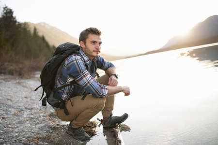 Young man, hiking, crouching by lake, taking in the view LANG_EVOIMAGES