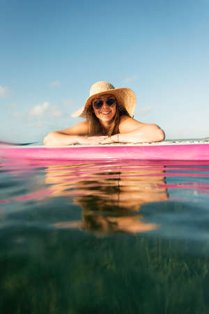 Surface level portrait of young woman and paddleboard, Islamorada, Florida, USA