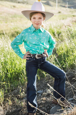 top 7: Girl wearing cowboy hat with hands on hips, portrait LANG_EVOIMAGES