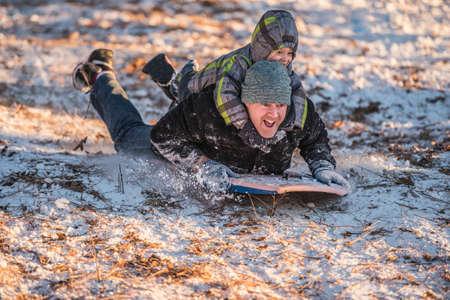 Portrét usmívající se otce a syna sáňkovat svahu ve sněhu LANG_EVOIMAGES