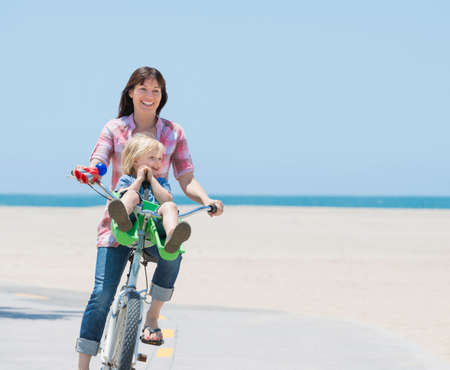 Woman and son cycling on beach, Venice, California, USA