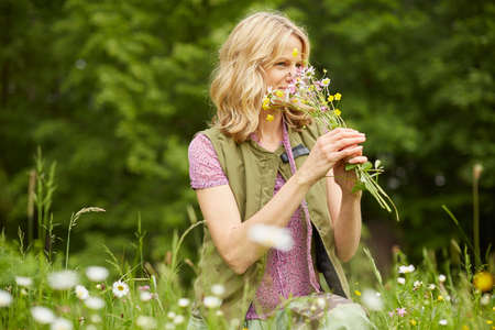 Mature woman in garden, smelling flowers LANG_EVOIMAGES