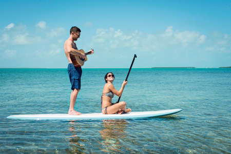 Young couple paddleboarding and playing guitar, Islamorada, Florida, USA LANG_EVOIMAGES