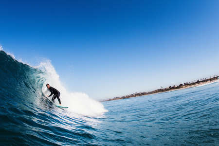 Mid adult male surfer surfing curved wave, Carlsbad, California, USA