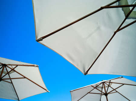 shadowed: Low angle view of parasols and blue sky