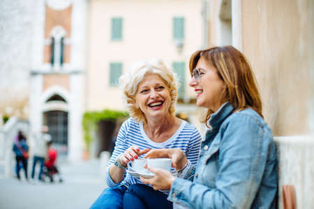 sidewalk talk: Two mature female friends talking and drinking coffee at sidewalk cafe, Tuscany, Italy LANG_EVOIMAGES