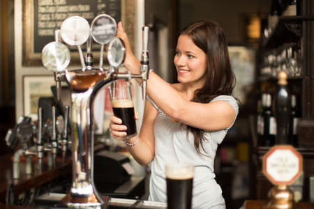Mid adult woman working in public house, serving drinks