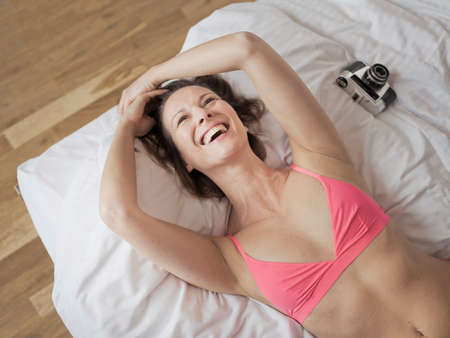 liberating: Overhead view of mature woman lying on bed wearing bra